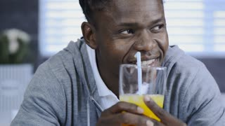 African American man drinking orange juice in modern lifestyle kitchen