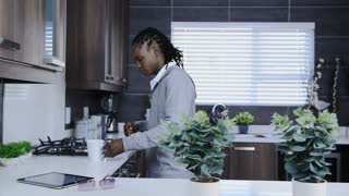 African American man drinking warm drink in modern kitchen