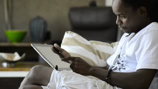 african american man in living room viewing a tablet computer
