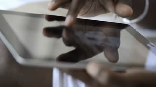 African American man using tablet computer for information.