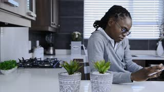 african american man using tablet computer in modern kitchen