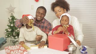 African American parents helping children assemble christmas gifts