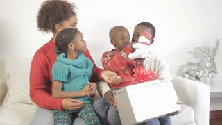 African American son opening Christmas gifts with family