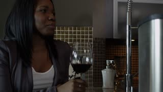 African American woman drinking wine and laughing at something she sees on the internet