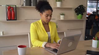 African businesswoman working on the computer in modern room with creative interior. Female concentrated on her job. Multicultural model young and professional wearing in formal yellow jacket.