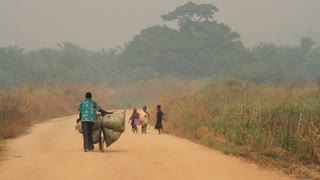African Dirt Road With Bicyclists And Children
