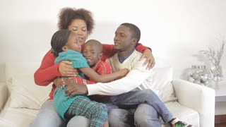 African family hugging each other on the couch