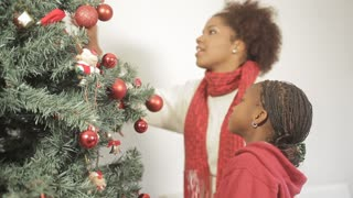 African girl with her mom decorating the christmas tree