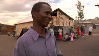African Man Talking with Metal Houses in Background