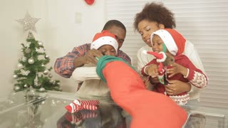 African parents helping kids open christmas stocking presents