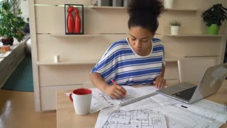 African young designer works at the creative modern agency. Professional female checking architectural sketch at the working place with laptop pencil line equipment for drawing and draftsmanship. On