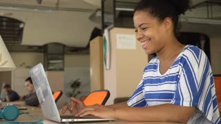 African young girl typing on the computer turns her head and smile. Near businesswoman sitting her colleagues at the work space. Mixed race employee wearing in casual top. Laughing girl sitting