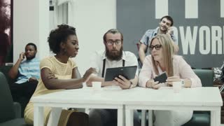 Afro-American woman and two caucasian colleagues using tablet in office