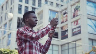 Afro american young man taking photo of skyscrapers with his smartphone