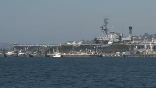 Aircraft Carrier zoom out across San Diego Harbor