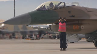 Aircraft Marshaller signals to the pilot of an F-16 fighting falcon at Red Flag