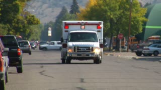 Ambulance With Lights Driving Down Street