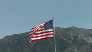 American flag blowing in the wind with a mountain behind it