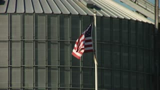 American Flag Waves In Front Of Grain Elevator