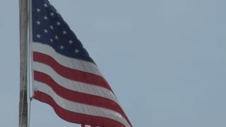 American Flag Waving in Dull Blue Sky