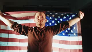 American patriotic male with American flag in hands on the back looking straight in the camera. Patriotic concept. Movement shot