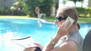 Angry business couple sitting by the swimming-pool and talking on cellphone