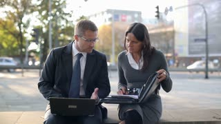 Angry business couple with laptop and documents in the city, steadycam shot