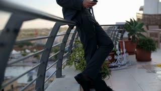 Angry businessman talking on cellphone on the terrace, crane shot