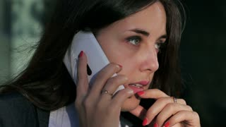 Angry businesswoman chatting on cellphone outside
