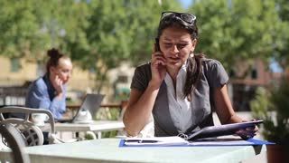 Angry businesswoman with cellphone and documents in the cafe
