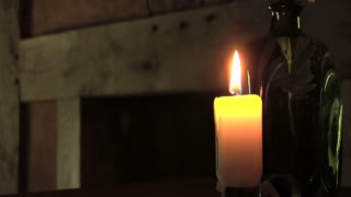 antique candle burns inside wooden cabin