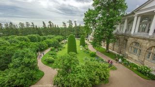 Antique gallery with sculptures and garden in the Catherine park timelapse, Saint-Petersburg. Floral compositions, trees, bushes. Cloudy summer day