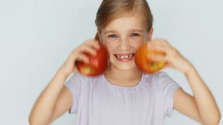 Apple eyes. Girl playing with apple and laughing. Thumb up. Ok. Closeup
