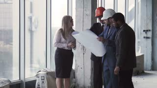 Architects holding plan of building and talking while wearing hardhats
