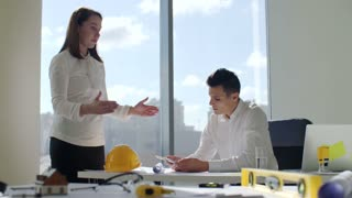 Architects sits by the table in white modern office construction company in front of large panoramic window. city skyline background. They working on construction project of building