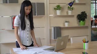 Asian architect standing in the creative office agency and drawing architectural design. On the wooden table plan of building laptop pencil and line. Vietnamese young professional designer works at