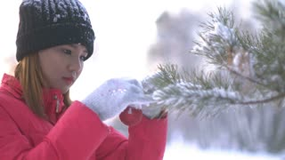 Asian Girl decorating Christmas tree in forest 4k UHD (3840x2160)