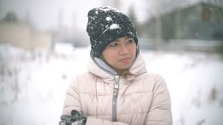 Asian Girl shivering from the cold in winter during snowfall slowmotion