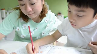 Asian Mom is helping her son to do homework of the school