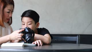 Asian mother and son looking and shoot with DSLR camera together