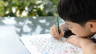 Asian Smiling child studying and doing his homework while holding his pencil drawing in paper .