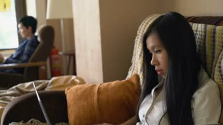 Asian young woman sits on the sofa reading documents and typing on the computer in the creative office. Professional manager with long black hair wearing in formal clothes. Female with short haircut