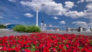 Astana, Kazakhstan Stele monument Kazakh Eli with bird Samruk and Palace of Independence timelapse hyperlapse and red flowerbed in foreground. Kazakhstan gained independence in 1991. The height of the