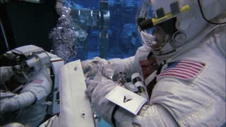 Astronaut in Suit Closing Container Underwater