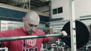 Athlete in red t-shirt lift heavy weight bar does exercises workout  in gym with bar