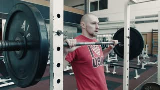 Athlete in red t-shirt lift heavy weight bar in gym on exercise machine