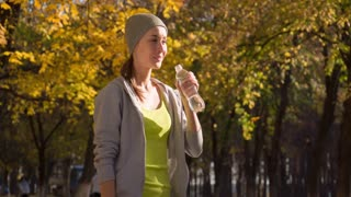 Athletic beautiful sports woman is drinking pure water from the bottle refreshing herself after running in autumn park. Dolly shot. Slow motion 120 fps. 4k graded from RAW. UHD, Ultra HD resolution.