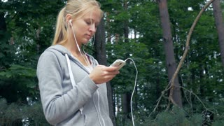 Attractive blond girl using a smartphone and listening to music
