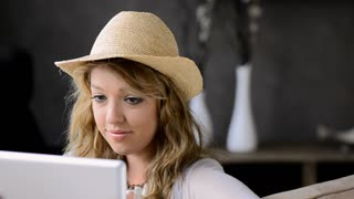 attractive blond girl with hat viewing tablet computer in apartment