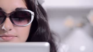 attractive brunette business woman working on tablet computer with reflective sunglasses